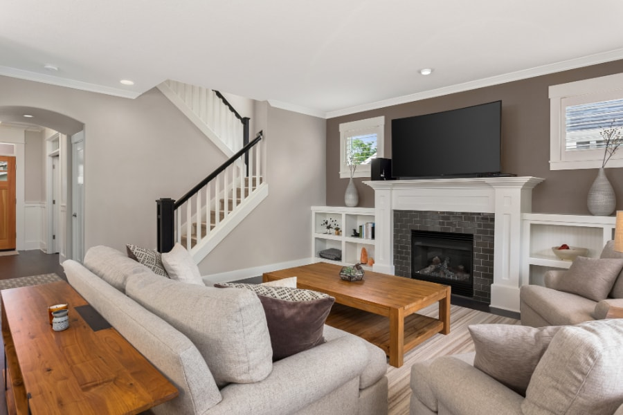 New lounge with stairs, fireplace, wood flooring, cream sofa and arm chairs at property in Swansea