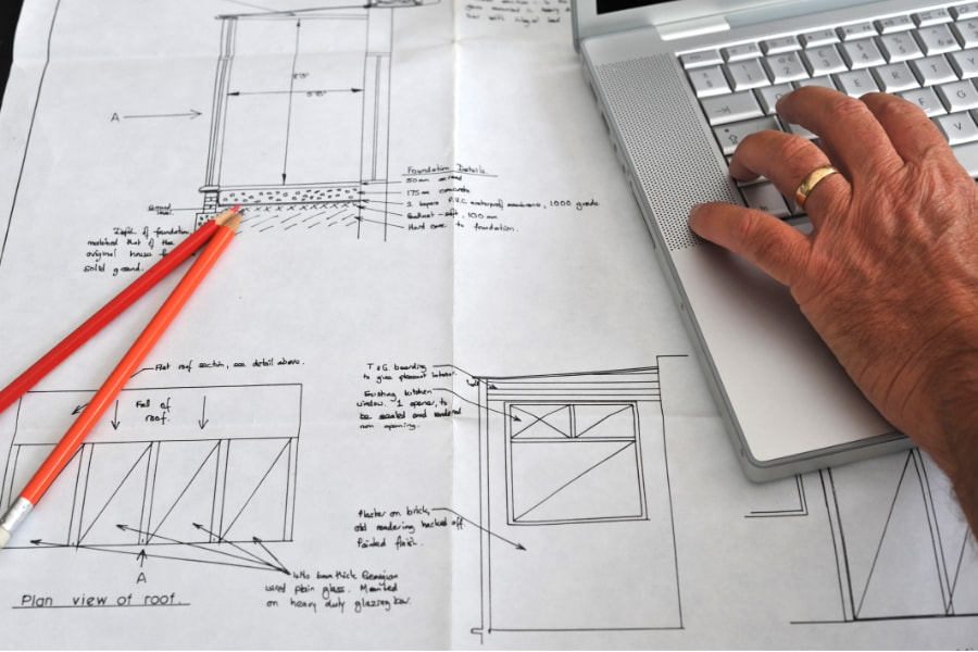 Architects drawing of home extension with 2 orange pencils and man on laptop doing some admin work