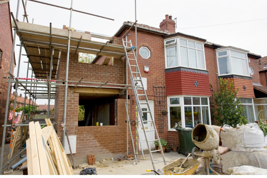New doiuble extension being added to semi-detached property. Scaffolding surrounding new extension with ladder leading to second storey