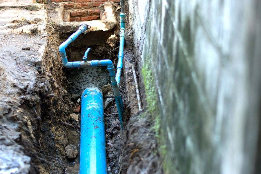 New domestic drainage pipe being installed. Blue soil pipe laying in trench in readiness to be connected to existing foul system in property in Swansea