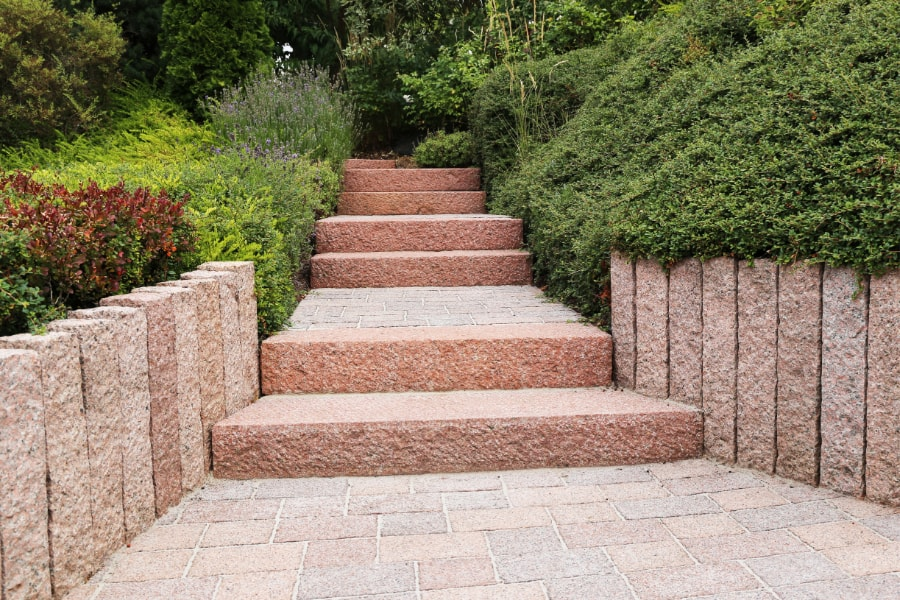 Garden path with wooden sleepers running along each side leading to 6 wide garden steps with shribs and greenaryGarden steps
