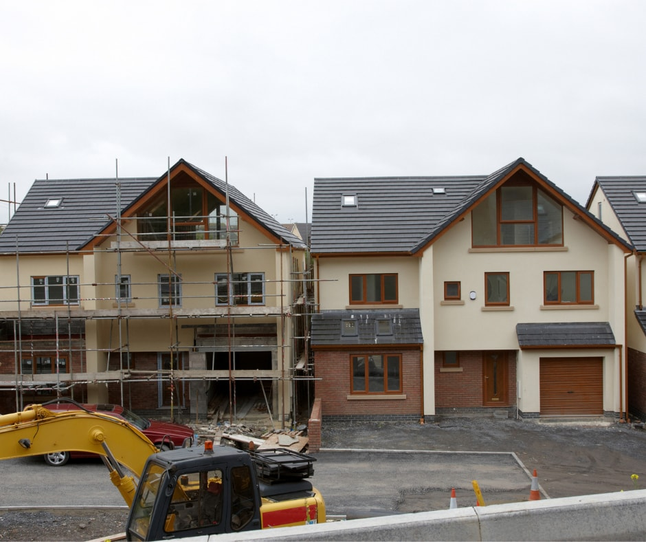 2 New Build Detached Houses with cream render. JCB in front of properties completing work on pavements and road