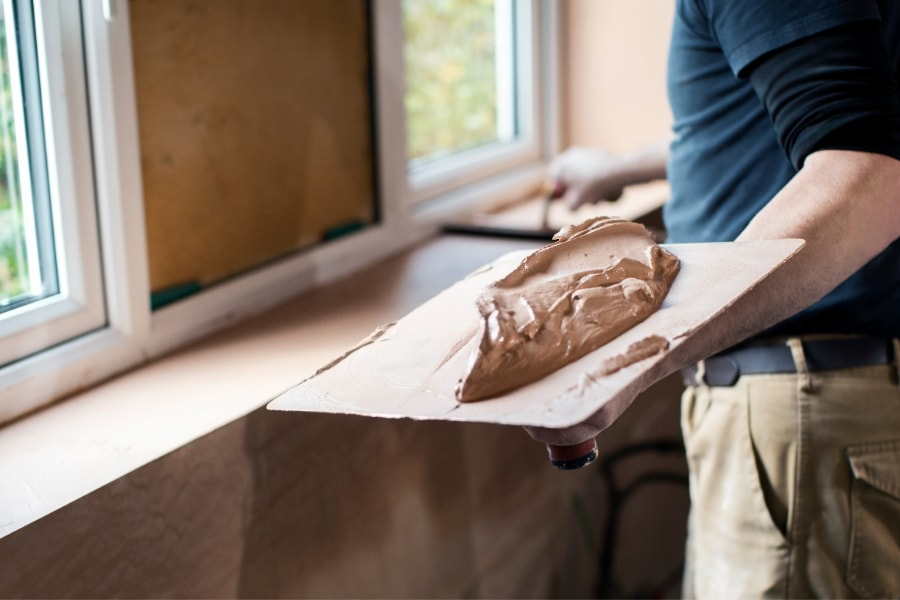 Plaster with hawk full of pink plaster ready to plaster new extension for house renovation in Swansea