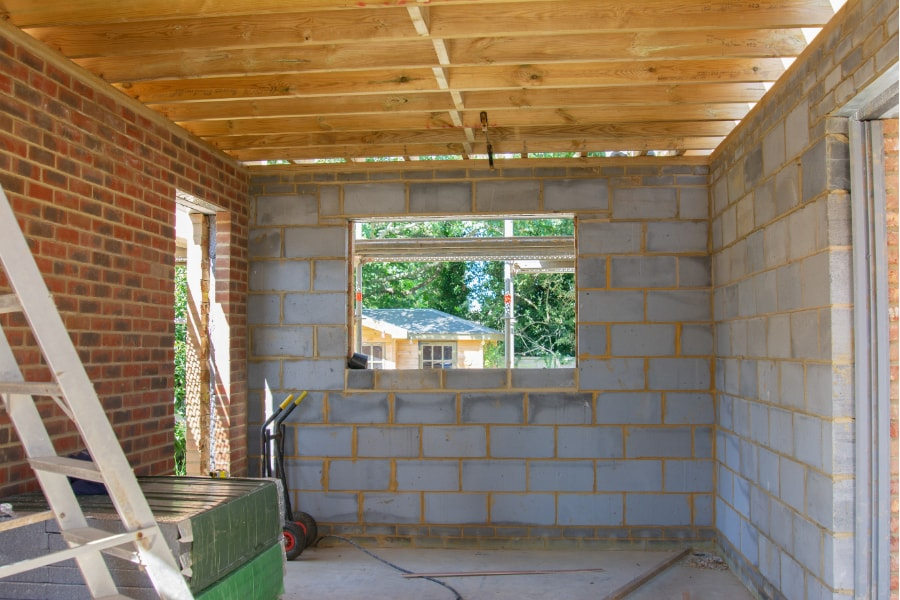 early stages of new single storey extension including doorway, window and patio doors, Roof beams fitted double skin walls built